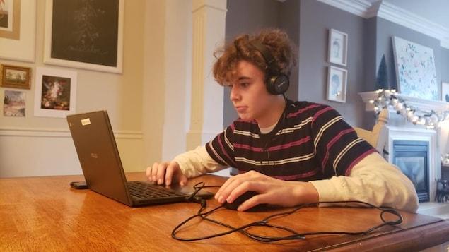 Étudiant à l'ordinateur avec des écouteurs.