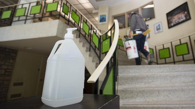 Un gros contenant de gel désinfectant devant un escalier.