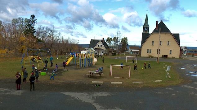 Les jeunes jouent dans l'espace entre l'école et l,église.