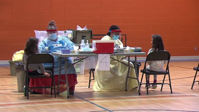 Deux jeunes filles assises à une table avec des infirmières manipulant des trousses de dépistage de la COVID-19.