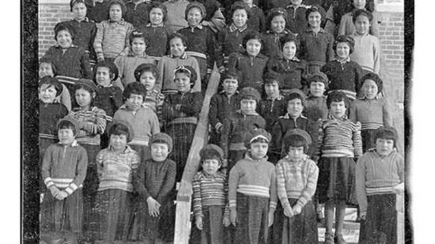 Fotografía de un grupo de niños indígenas de pie en las escaleras de la Escuela Residencial Beauval en Saskatchewan. Están acompañados por dos monjas grises. La fotografía fue tomada en invierno.