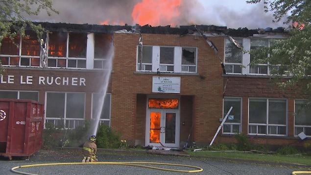 Un pompier arrose un immeuble en briques brunes en flammes.