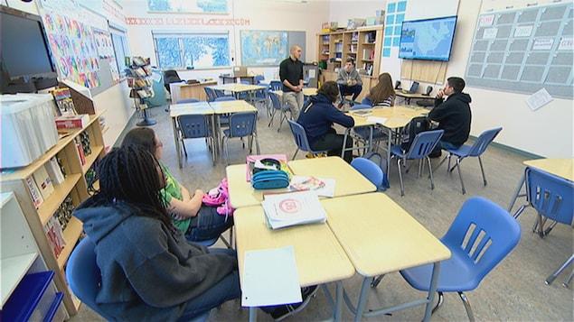 Une classe de secondaire avec six élèves parle à leur enseignant.
