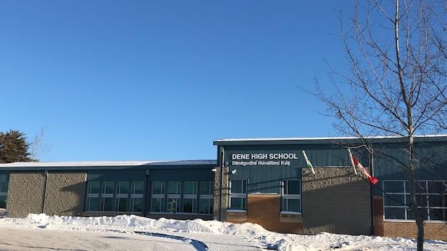 Un bâtiment bleu avec l'indication Dene High School et son équivalent en une langue autochtone, lors d'une journée ensoleillée.