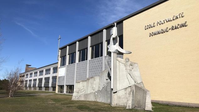 Une école vue de l'extérieur avec une statue argent.