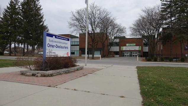 Édifice de l'école et en avant-plan, une affiche où on peut lire le nom.
