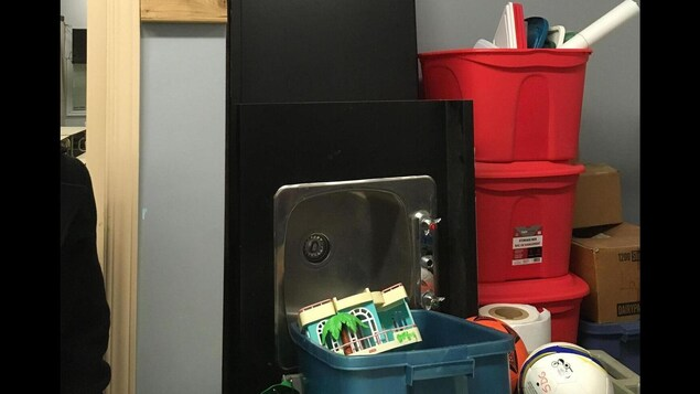 Des boîtes de plastique, un évier, un miroir et d'autres objets sont empilés dans une pièce.