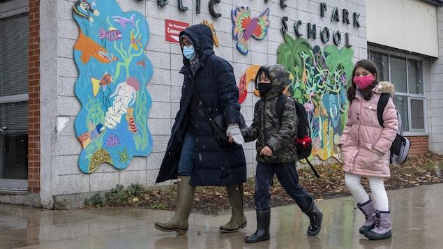 Une mère, sa fille et son fils marchent devant l'École Thorncliffe Park.