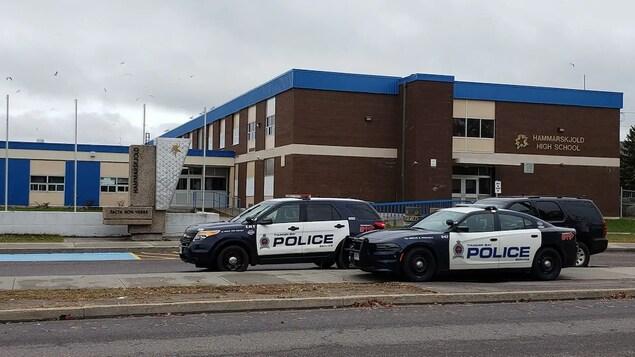 Trois voitures de la police de Thunder Bay sont garées devant une école.