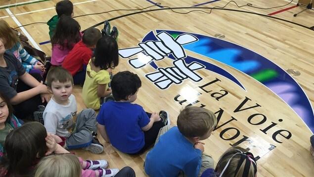Des enfants assis par terre dans un gymnase . Sur le plancher est imprimé le logo de l'école, deux inukshuks avec des aurores boréales.