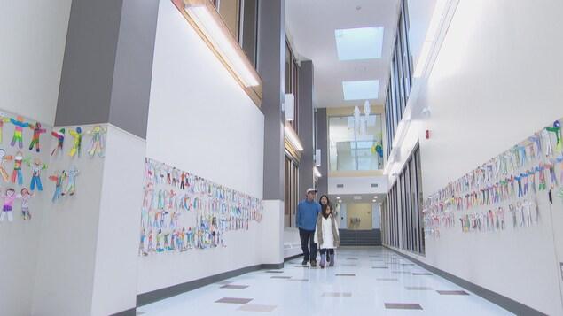Une famille arpente un couloir neuf et décoré de l'École élémentaire catholique Sainte-Geneviève, à Ottawa.