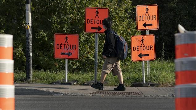 Un écolier marche près de pancartes indiquant des détours, mais dans des directions différentes.