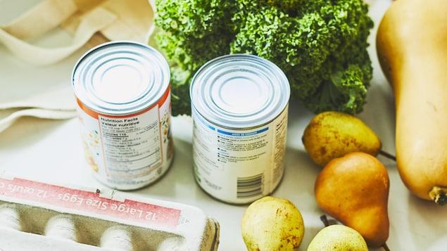 Sur un comptoir de cuisine sont déposés plusieurs aliments comme des œufs, du brocoli, des poires et des légumineuses en cannes.
