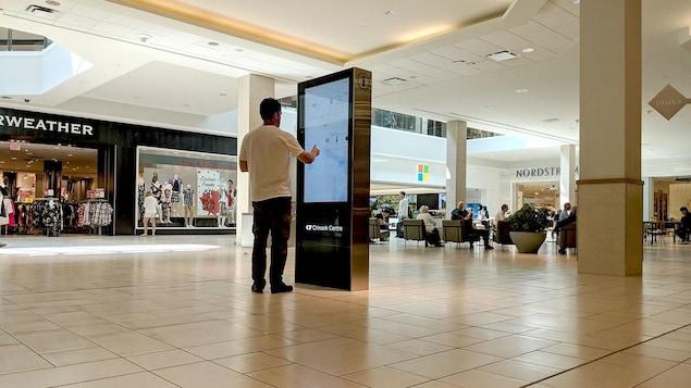 Un visiteur tape sur l'écran d'orientation tactile avec son doigt dans un centre commercial.