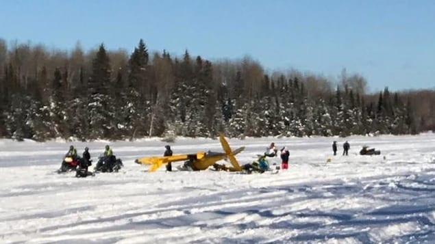 Des motoneigistes sont regroupés autour d'un petit avion qui s'est écrasé sur un lac gelé.
