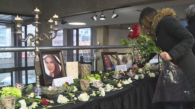 一个年轻人向遗像献花。