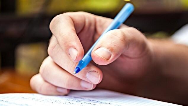 une main avec un crayon