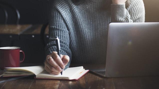Une femme est assise devant un ordinateur et écrit avec un stylo dans un carnet.