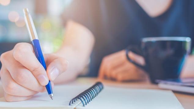 Une personne écrit avec un stylo dans un cahier.