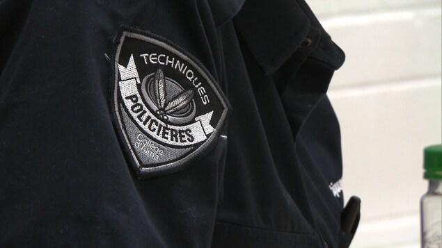 Un écusson sur lequel on peut lire « Techniques policières, Collège d'Alma ».
