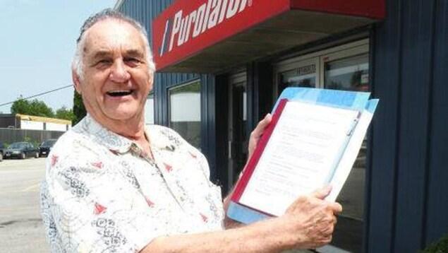 Ed Deibel qui tient un document devant les bureaux de Purolator.