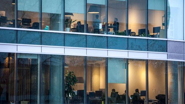 Au travers de la façade vitrée d'un édifice où se trouvent des bureaux, des gens travaillent.