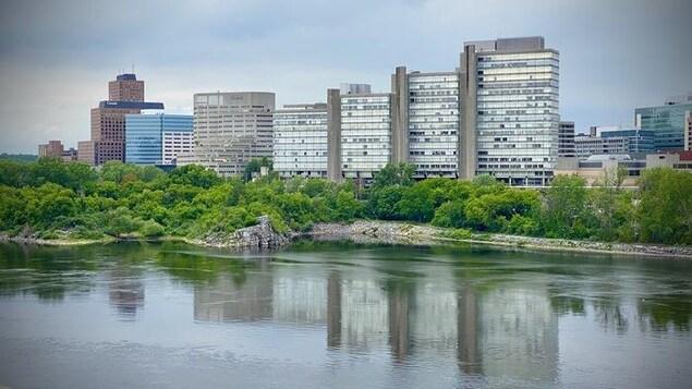 Des édifices vus d'une rivière.