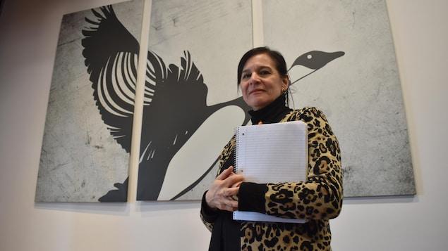 Elle pose devant un tableau d'oie en vol.