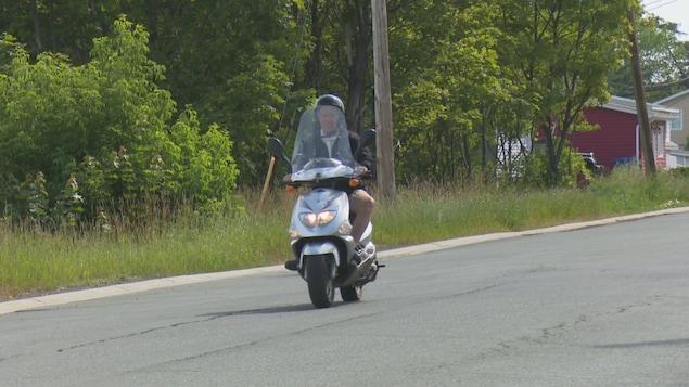 Edmond Diotte roule au guidon de son scooter.