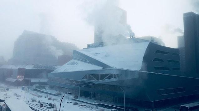 Scène froide de la nouvelle bibliothèque d'Edmonton. Les bâtiments dégagent un épais panache de fumée blanche.