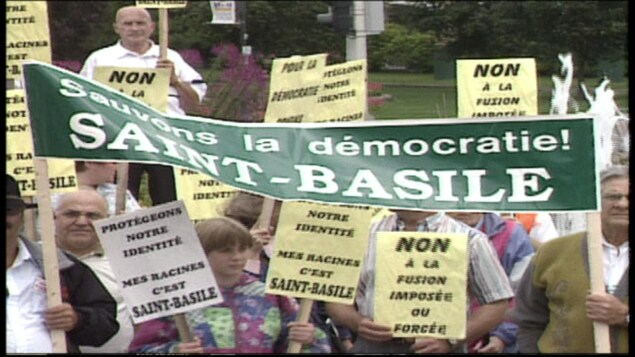 Image d'archives de manifestants portant des pancartes contre la fusion