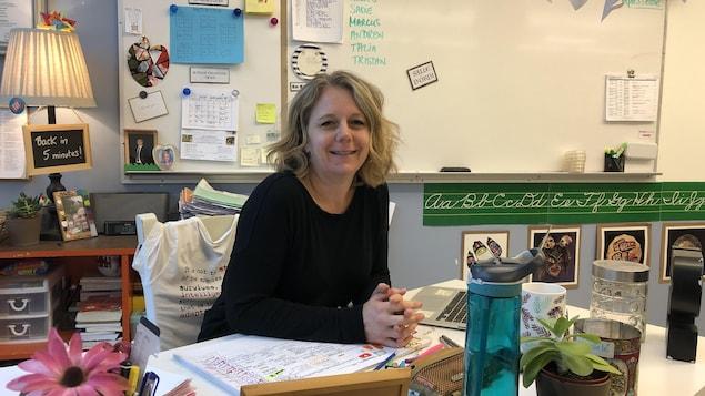 Une femme assise à son bureau dans une salle de classe.