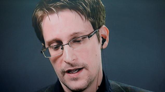 Edward Snowden, portant des lunettes, regardant vers le bas, au cours d'une allocution prononcée par vidéoconférence.