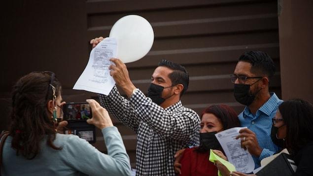 Edwin Espinal, a la izquierda, y el coacusado Raúl Alvares, a la derecha, saludan tras lograr su liberación en Honduras.