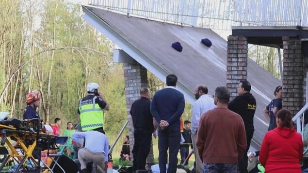 Une terrasse touche le sol, contemplée par une dizaine de personnes, dont un policier et un membre de l'équipe des secours.