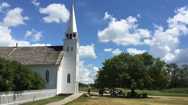 Une église blanche dans un champ en dessous d'un grand ciel des prairies.