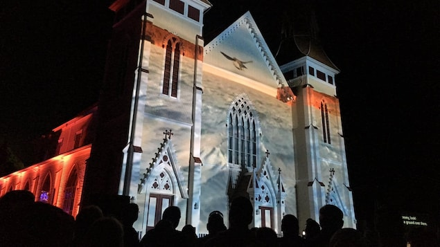 Des projections sur la façade d'une église le soir.