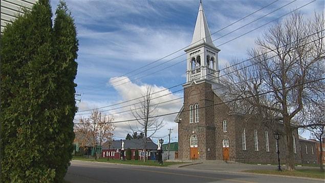 Un bâtiment religieux en brique grise se trouve au coeur de la municipalité.