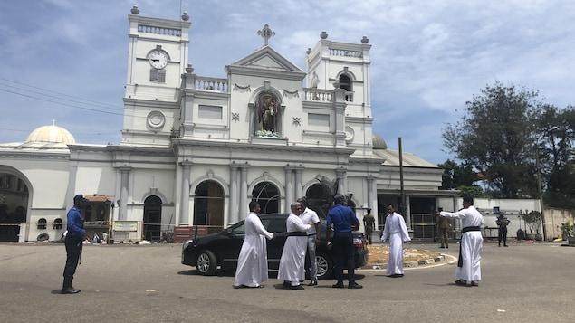 Des gens marchent devant une église blanche.