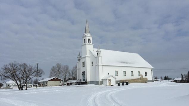 Une église blanche se détache sur un fond nuageux.