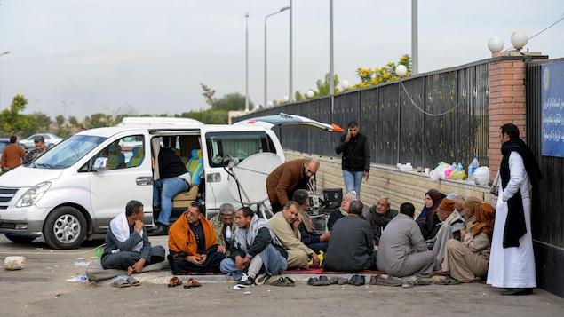 Des proches des victimes de l'attaque de la mosquée Al-Rwadah patientent devant un hôpital.