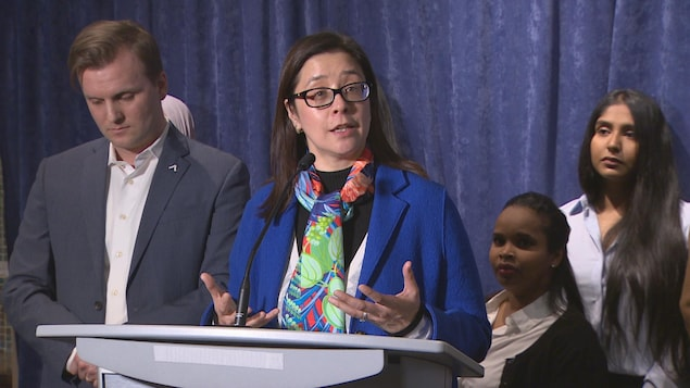 Une femme parle à un podium.