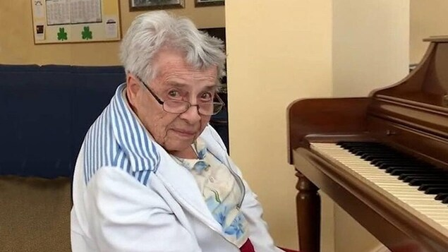 La femme est assise devant un piano et regarde la personne qui prend la photo.
