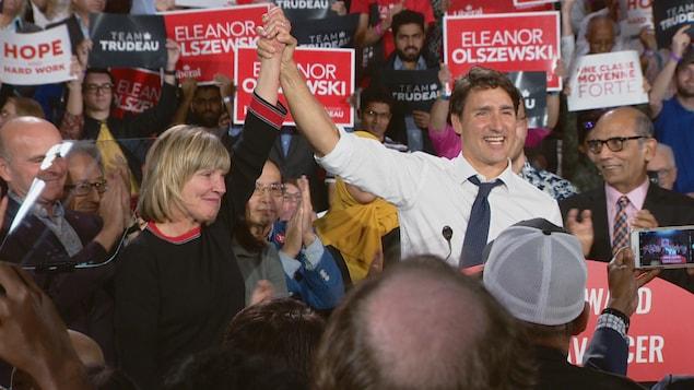 Justin Trudeau lève la main d'Eleanor Olszewski vers le ciel en signe de victoire.