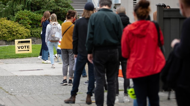 Une quinzaine de personnes font la file devant un bureau de vote.