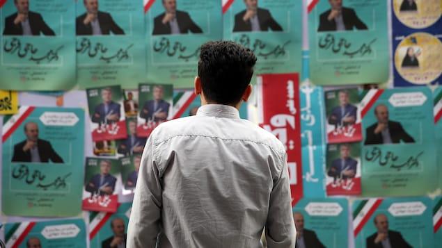 Un homme regardant un panneau d'affiches électorales