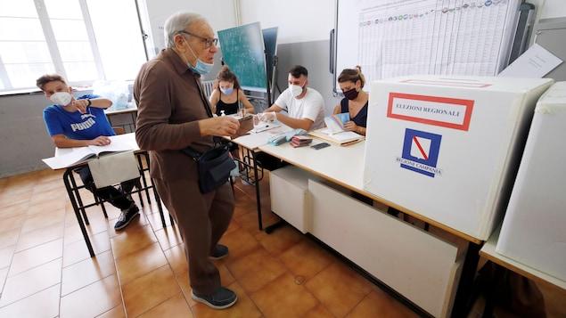 Un homme âgé s'apprête à déposer son bulletin de vote.