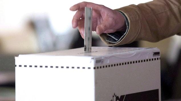 une main tient un bulletin de vote et la dépose dans une urne électorale.