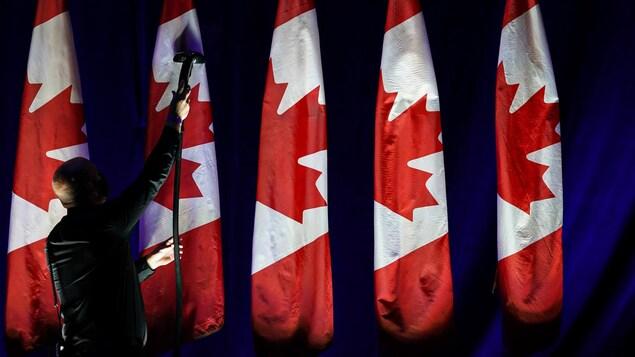 Un homme nettoie des drapeaux canadiens.