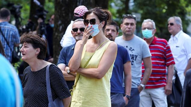 Des gens font la file à l'extérieur. Deux personnes sur sept portent un masque sur le nez et la bouche.